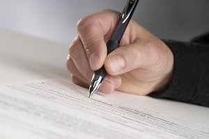 man hand holding a pen writing his signature knowing how long does title insurance last