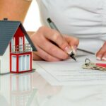 woman signs a contract to purchase a home with a real estate agent